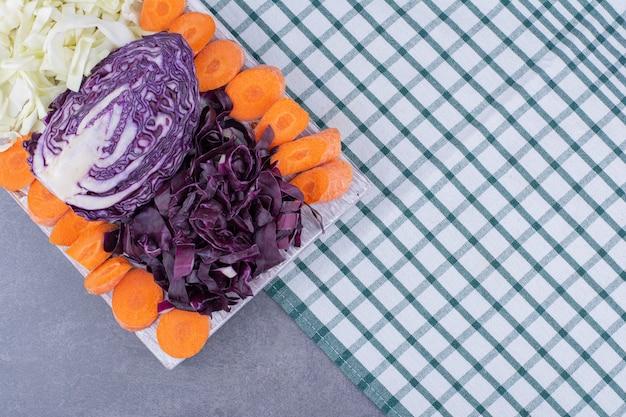 Chou haché et tranches de carottes sur un plateau.