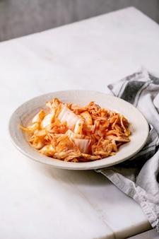 Chou kimchi apéritif fermenté traditionnel coréen fait maison servi dans une assiette en céramique sur une table en marbre blanc.