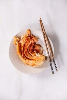 Chou kimchi apéritif fermenté traditionnel coréen fait maison servi dans une plaque en céramique avec des baguettes. mise à plat, espace de copie