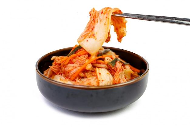Chou kimchi dans un bol avec des baguettes sur fond blanc, vue de dessus.