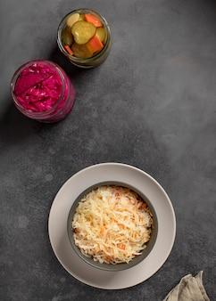 Chou mariné dans un bol et légumes fermentés dans des bocaux en verre surface gris foncé, vue de dessus,
