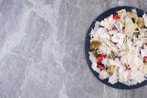 Chou mariné avec divers légumes sur assiette sombre.