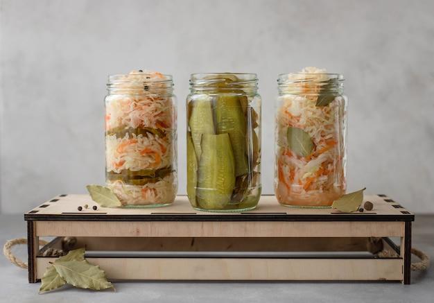 Chou mariné maison et concombres sur une boîte en bois aliments végétariens conservés fermentés surface grise