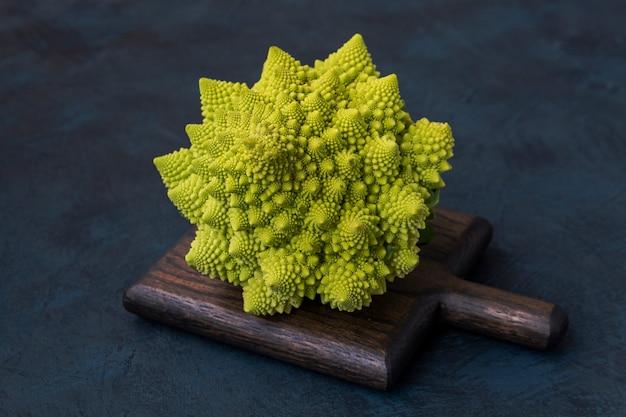 Chou roman brocoli roman sur une planche à découper contre une table sombre alimentation végétarienne mode de vie sain