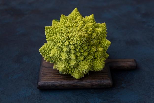 Chou romanesco brocoli roman sur une planche à découper contre une table sombre nourriture végétarienne il