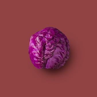 Chou rouge cru présenté sur fond rouge, légume, isolé. de la série de choux de couleur