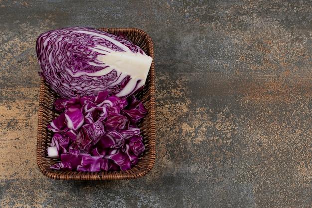 Chou rouge délicieux dans le panier en osier sur la surface en marbre