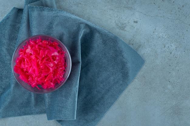 Le chou rouge fermenté se trouve dans un bol sur un morceau de tissu, sur la table bleue.