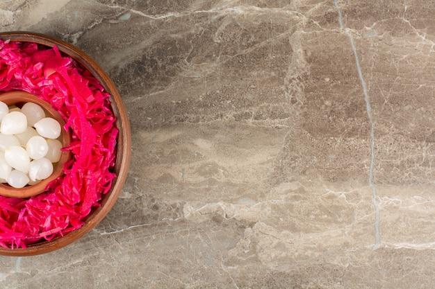 Chou rouge mariné avec des gousses d'ail placés sur une table en pierre.