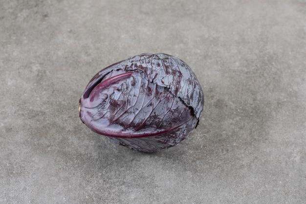 Un chou rouge mûr frais entier placé sur une table en pierre.