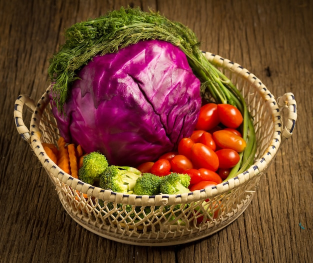 Chou rouge. petites tomates. aneth. dans un panier en bois. sur cuisine en bois. matin. le coucher du soleil