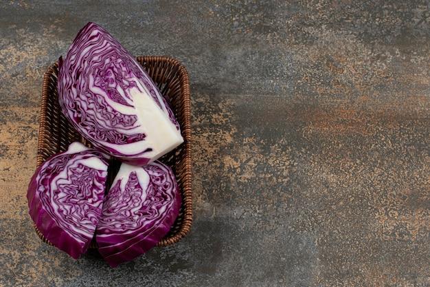 Chou rouge savoureux dans le panier en osier sur la surface en marbre