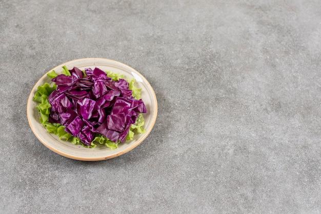 Chou rouge tranché sur une assiette, sur la table en marbre.