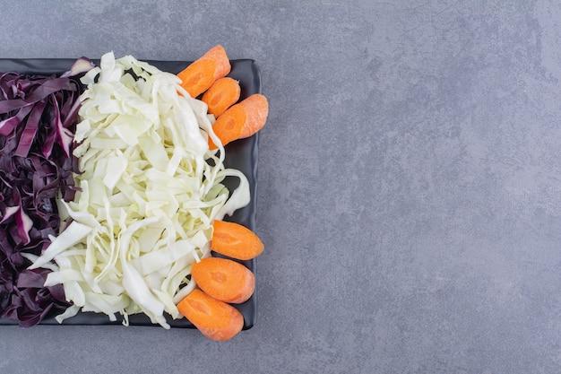 Chou violet et blanc haché avec des tranches de carotte