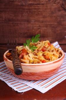 Choucroute aux saucisses et lentilles dans un bol en argile