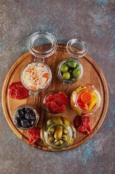 Choucroute, carottes marinées, concombres marinés, olives et olives marinées, tomates séchées dans des bocaux en verre