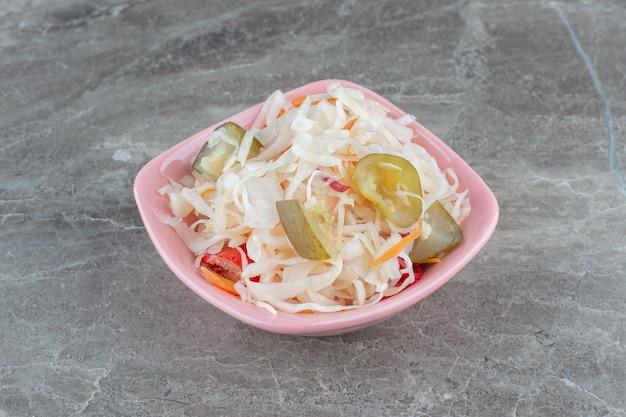 Choucroute. chou et carottes râpés dans un bol rose.