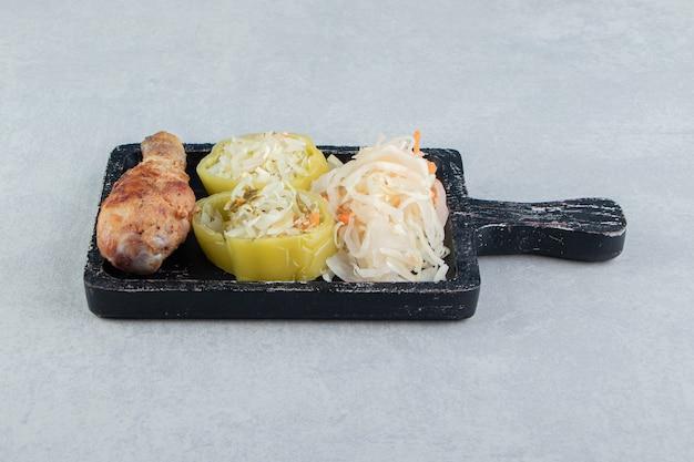 Choucroute et cuisse de poulet frit sur tableau noir.