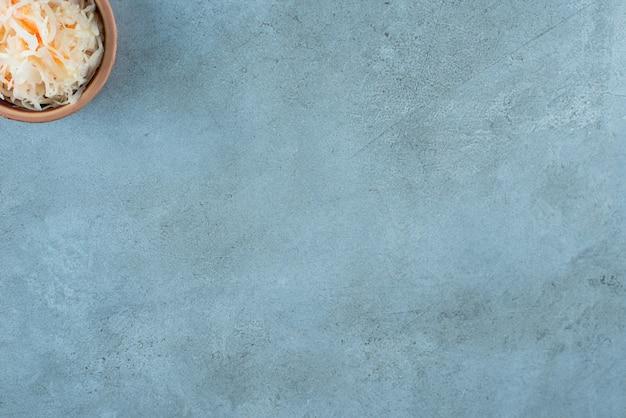 Choucroute fermentée aux carottes dans un bol en argile, sur la table bleue.