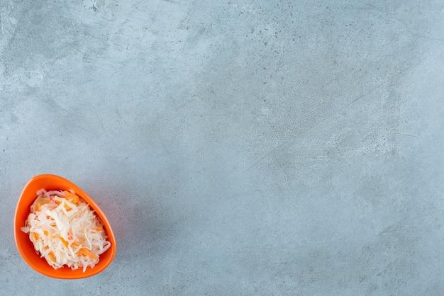 Choucroute fermentée aux carottes dans un bol en plastique , sur la table bleue.