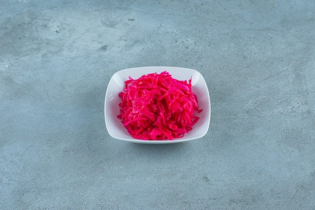 Choucroute fermentée rouge hachée savoureuse dans un bol , sur la table bleue.