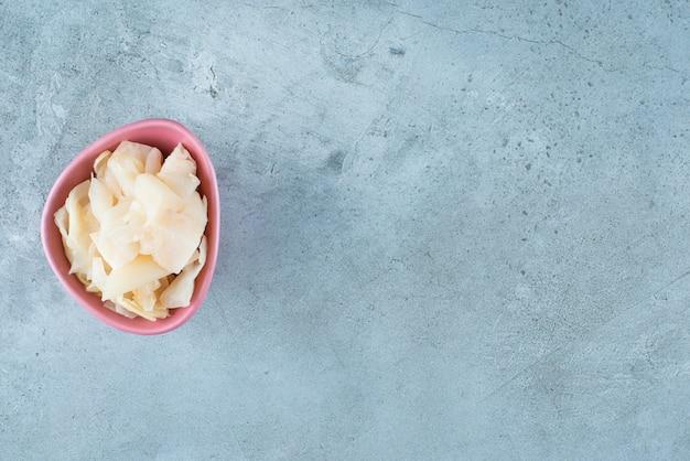 Choucroute fermentée tranchée avec des carottes dans un bol en plastique , sur la table bleue.