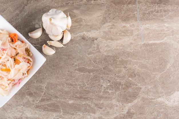 Choucroute de légumes fermentés placée sur table en pierre.