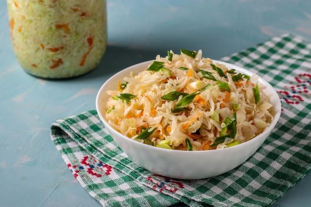 Choucroute maison aux carottes et oignons verts dans un bol sur un fond bleu clair, les aliments fermentés, vue du dessus, mise à plat