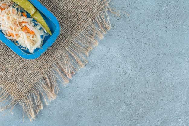 Choucroute et piment en conserve sur une plaque en bois sur la texture , sur la table en marbre.