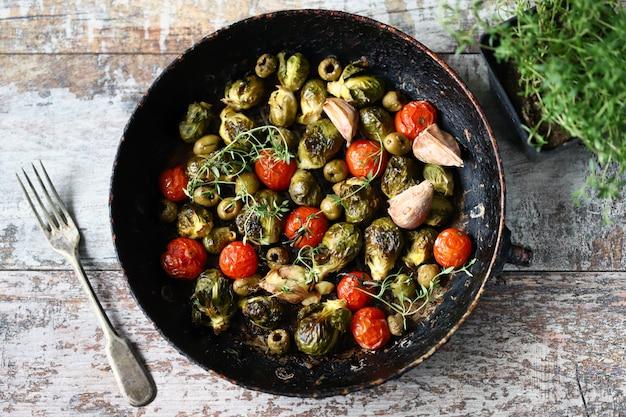 Choux de bruxelles au four dans une poêle avec tomates cerises, ail et olives. nourriture saine. régime végétalien. casserole de légumes.