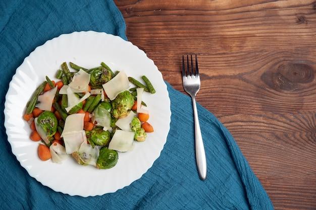 Choux de bruxelles frits carottes et haricots verts reposent sur une plaque blanche qui se dresse sur une table en bois.