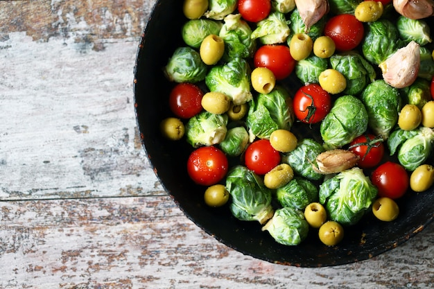 Choux de bruxelles avec légumes et herbes dans une casserole. cuisson des choux de bruxelles. nourriture vega. mise au point sélective.
