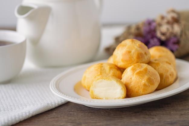 Choux à la crème maison ou crème eclair ou choux servi avec du thé sur une table en bois.