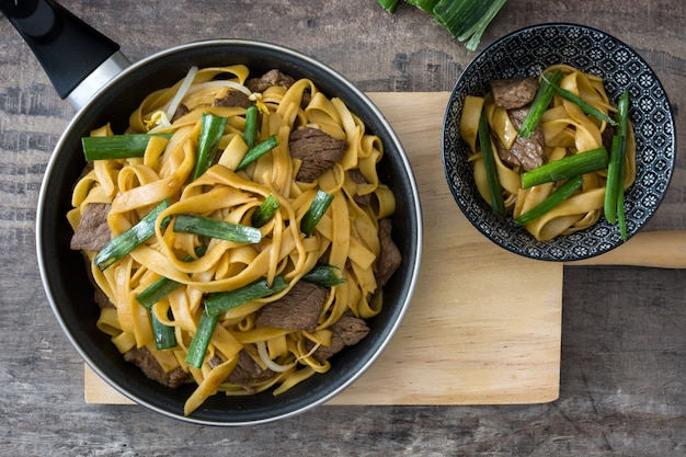 Chow mein au boeuf dans une poêle sur la vue de dessus de table en bois