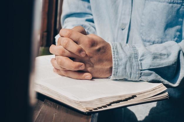 Le chrétien tient la bible entre ses mains. lire la bible. le concept de foi, spiritualité et religion
