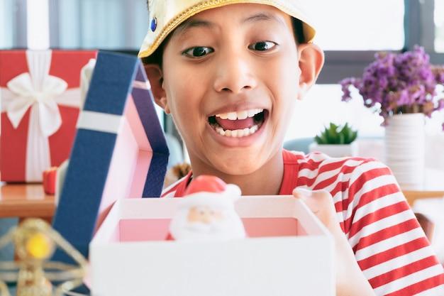 Christmas little boy porter avec des ornements décoratifs et des cadeaux de noël