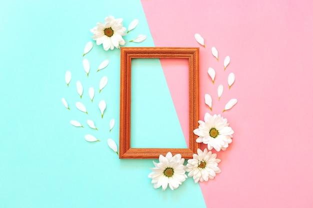 Chrysanthème blanc avec cadre en bois sur fond rose et menthe. vue de dessus