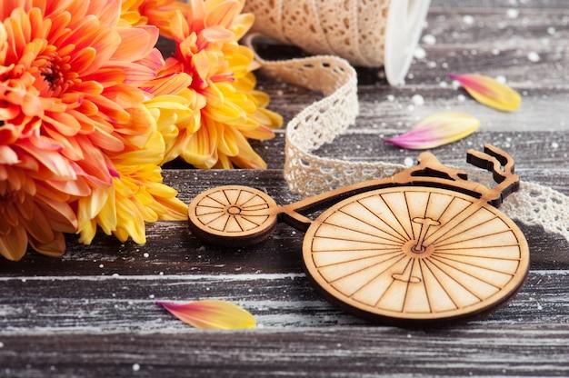 Chrysanthème orange et vélo en bois