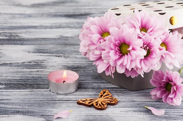 Chrysanthème rose dans une boîte cadeau, bougie allumée et papillon