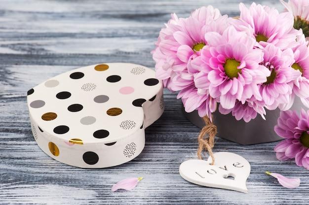Chrysanthème rose dans une boîte cadeau, coeur