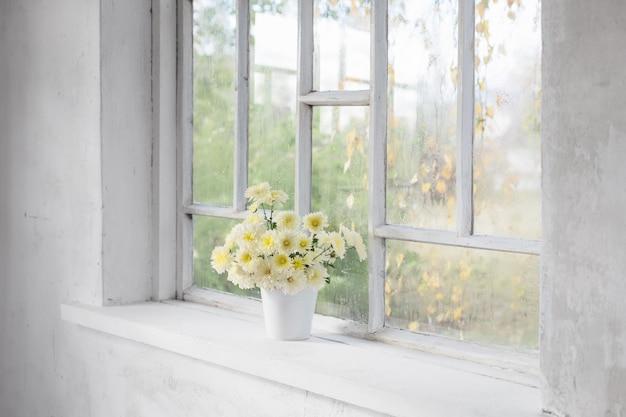 Chrysanthèmes dans un vase sur le rebord de la fenêtre en automne