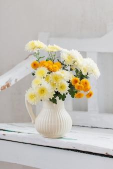 Chrysanthèmes jaunes en cruche sur vieux banc en bois blanc