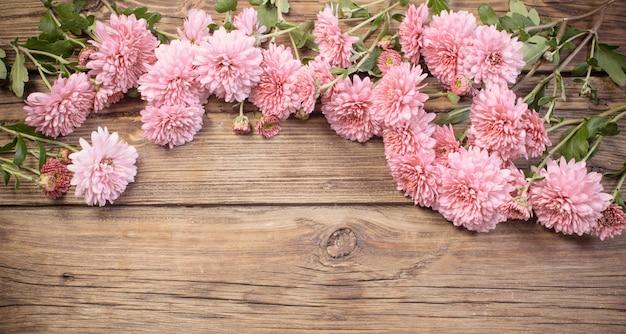 Chrysanthèmes roses sur fond de bois foncé