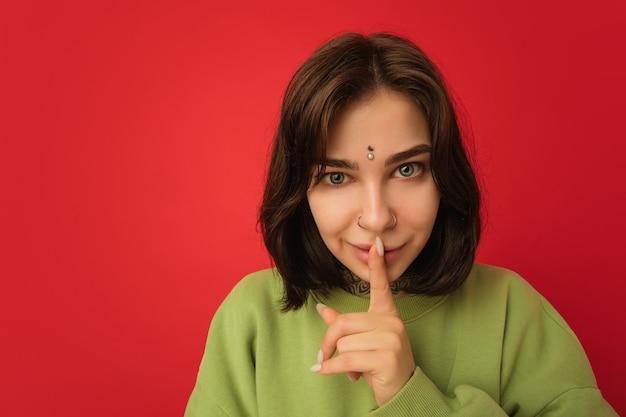 Chuchotant secrètement. portrait de femme caucasienne isolé sur mur rouge avec fond. beau modèle féminin en sweat à capuche vert. concept d'émotions humaines, expression faciale