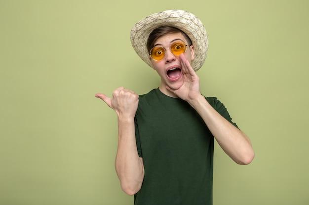 Des chuchotements suspects pointent sur le côté d'un jeune beau mec portant un chapeau avec des lunettes isolé sur un mur vert olive avec espace pour copie