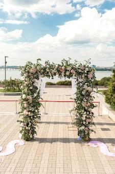 Un chuppah festif décoré de belles fleurs fraîches pour une cérémonie de mariage en plein air
