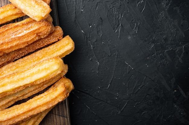 Churros au chocolat, cusine traditionnelle espagnole, sur fond noir, vue de dessus à plat avec un espace pour le texte, copyspace