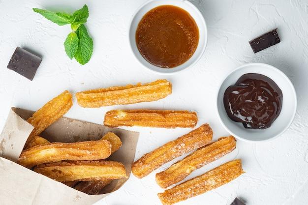 Churros au sucre et sauce au chocolat, sur fond blanc, vue de dessus à plat