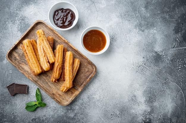 Churros au sucre et sauce au chocolat, sur fond gris, vue de dessus à plat avec un espace pour le texte, copyspace