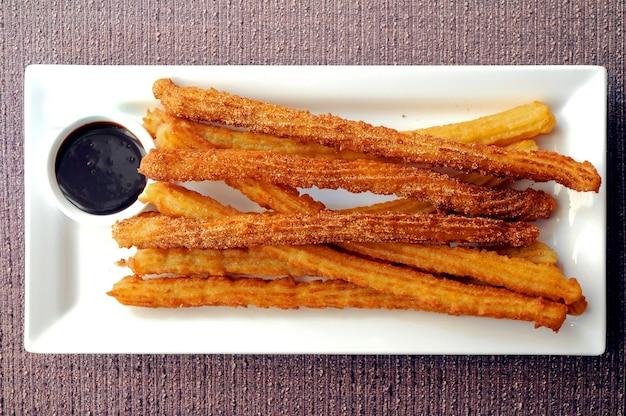 Churros aux beignets espagnols fraîchement préparés avec sauce au chocolat noir